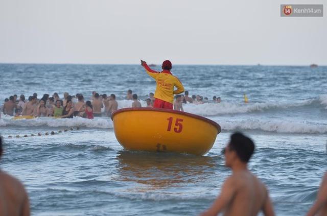 Một nhân viên cứu hộ chèo thuyền ra hiệu cho du khách tránh nguy hiểm trong lúc vui chơi, tắm biển. Ảnh: Phương Thảo