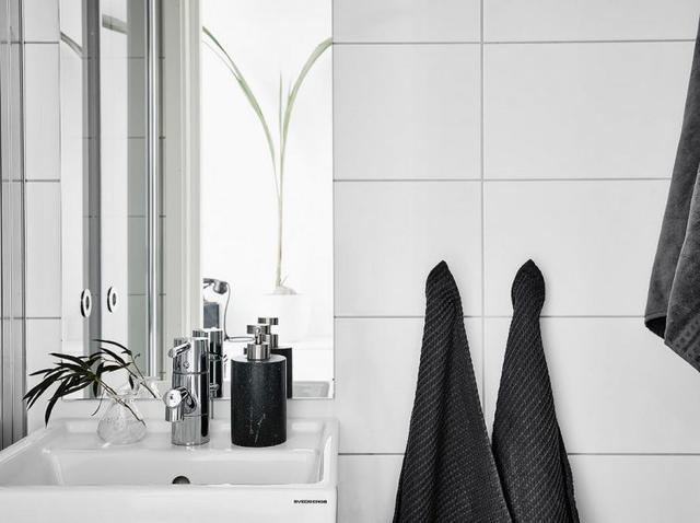 Khu vực vệ sinh sáng bóng với gạch ốp tường trắng cao sát trần.