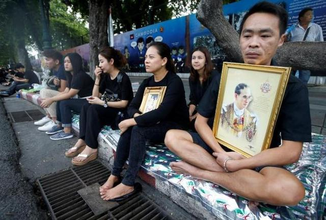 Bên ngoài các con đường, người dân Thái Lan trong trang phục màu đen, tay ôm di ảnh của Vua với dòng nước mắt nghẹn ngào.
