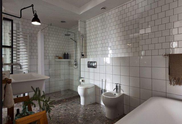 Nhà vệ sinh thoáng rộng, sạch bóng với gạch ốp cao sát trần.