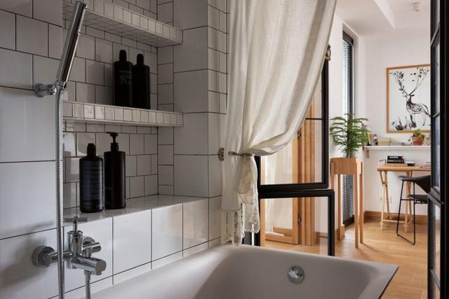 Bồn tắm được ngăn cách với không gian bên ngoài bằng một tấm rèm trắng.