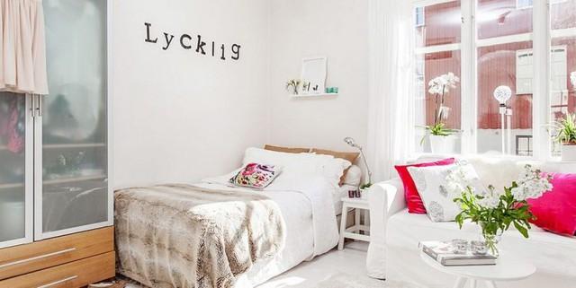 Những chiếc gối ôm màu đỏ và màu xanh của hoa lá nơi phòng khách gây sự chú ý đặc biệt trên nền trắng của cả căn hộ.