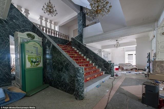 Trong khi đó, cầu thang lát đá cẩm thạch và đèn chùm vẫn còn nguyên vẹn.