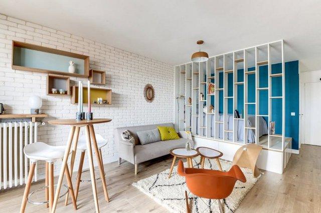 Không gian phòng khách được bố trí đơn giản với chiếc ghế sofa dài có chân tạo khoảng thông thoáng cho góc nhỏ.
