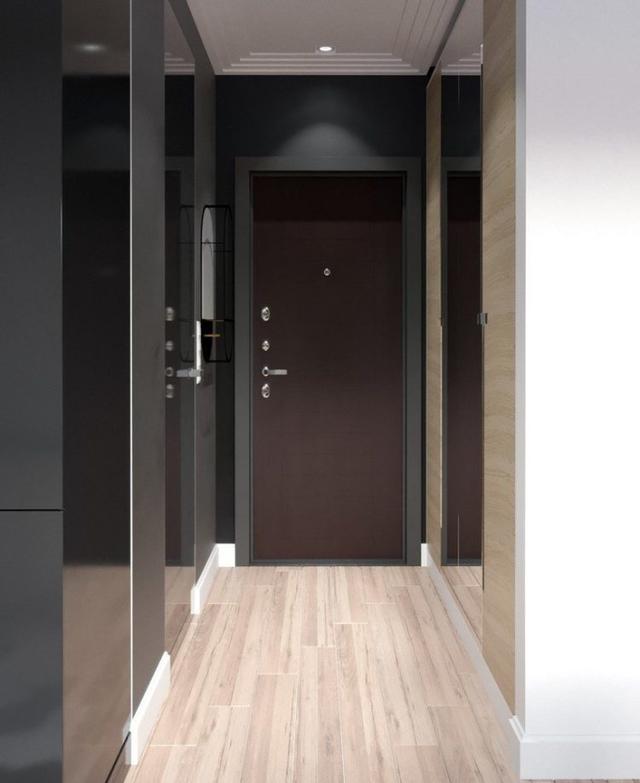 Lối vào nhà được thiết kế đơn giản với sự kết hợp hài hòa giữa tông màu sáng của sàn gỗ và màu tối của tường nhà, cửa ra vào.
