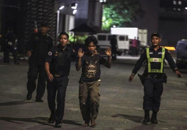 Cảnh sát và một nhân viên bảo vệ áp giải một nhân viên khách sạn khi thấy người này tại cửa khu phức hợp Resorts World Manila sau khi nổ súng xảy ra. Ảnh: Reuters