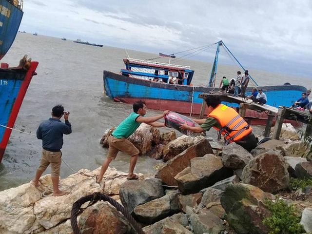 Người dân gom các dụng cụ còn sót lại trên chiếc tàu
