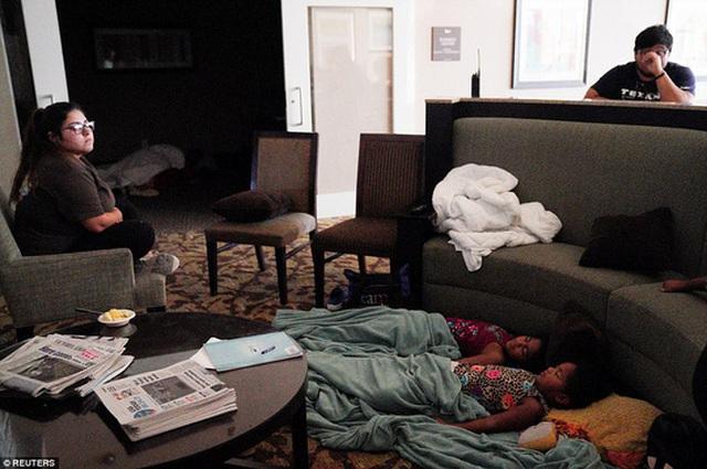 Trẻ em ngủ ở khu vực sảnh khách sạn trong lúc chờ bão Harvey đi qua ở TP Victoria, Texas, hôm 26-7. Ảnh: Reuters