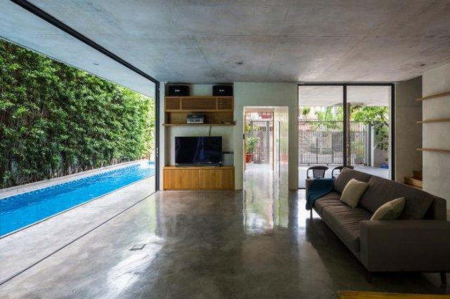 Tầng 1 thoáng rộng được thiết kế hoàn toàn mở với bếp, khu vực ăn uống và một phòng khách vô cùng lý tưởng nhìn ra bên ngoài có hồ bơi và một bức tường cây tuyệt đẹp.