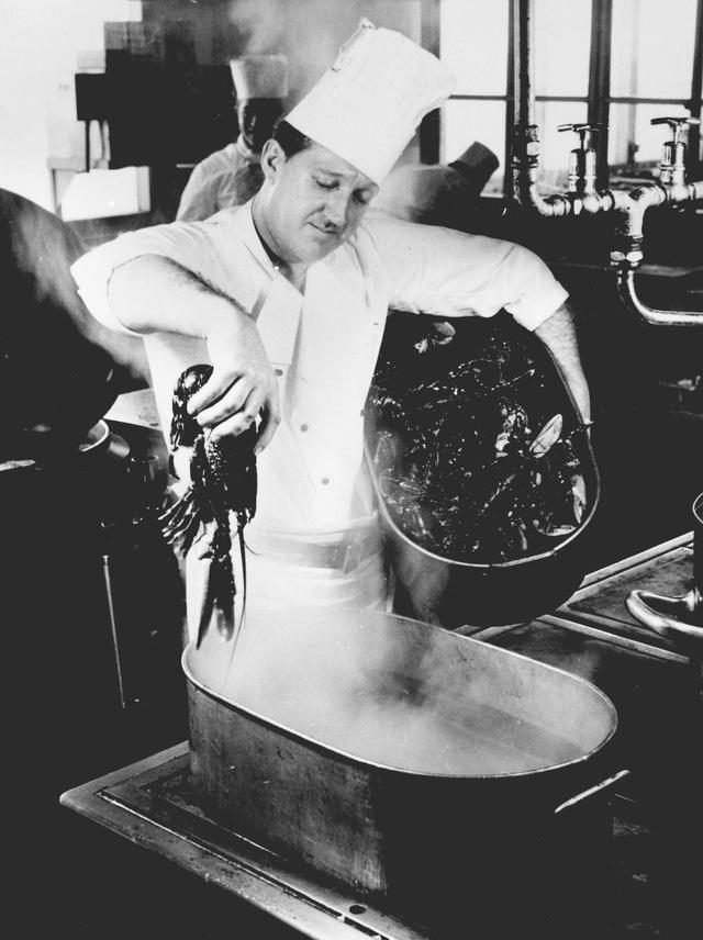 Bức ảnh này chụp vào khoảng giữa thập niên 50 đến 60, ghi lại cảnh một đầu bếp của hãng hàng không Scandinavian Airlines đang chuẩn bị… tôm hùm trong nhà bếp của sân bay Kastrup ở thành phố Copenhagen. Vâng, bạn không đọc nhầm đâu, tôm hùm là món có trong thực đơn máy bay thời bấy giờ đó…