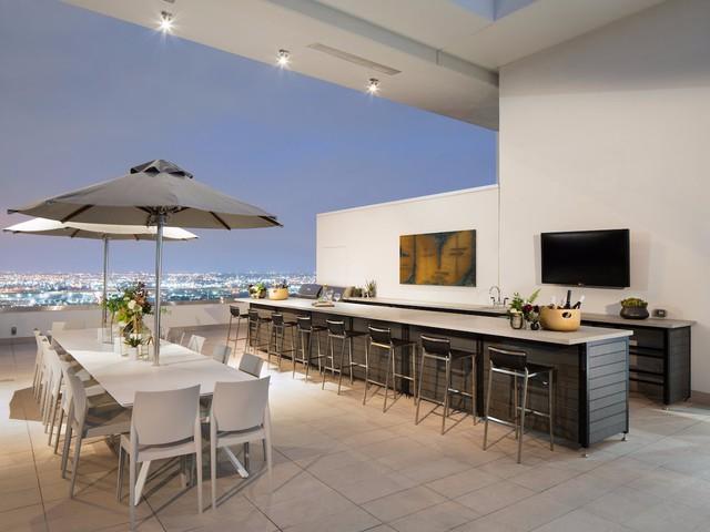 Trên tầng thượng của ngôi nhà là một không gian lý tưởng nhìn ra toàn cảnh thành phố. Nơi đây được bố trí một khu bếp khác với lò nướng BBQ và rất nhiều chỗ ngồi dành cho các hoạt động ngoài trời.