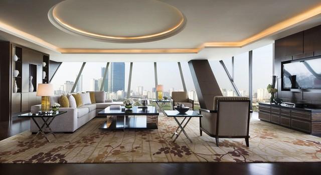 Phòng chiếm diện tích nhiều nhất là phòng khách với nội thất mang phong cách trầm nhờ sự kết hợp giữa đồ gỗ và thảm màu be, salon ghi sáng.