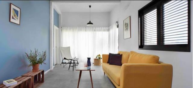 Không gian phòng khách được thiết kế đơn giản với bộ sofa màu vàng nổi bật kê sát tường. Chiếc bàn trà nhỏ với chân cao có thể dễ dang di chuyển để tạo khoảng vui chơi an toàn cho em bé.