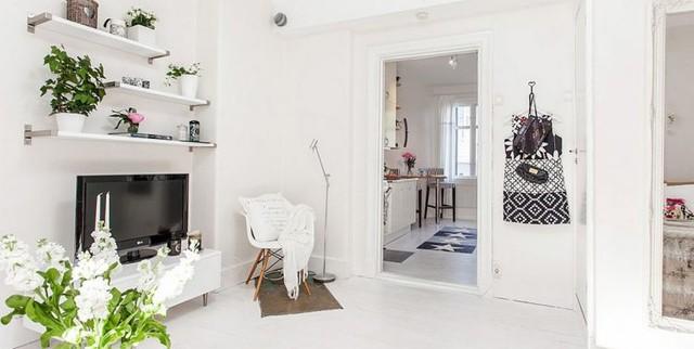 Đối diện phòng khách là chiếc ti vi với bàn trắng cùng những kệ gỗ trang trí. Từng chi tiết nhỏ của ngôi nhà đều được chủ nhân chau chuốt vô cùng cẩn thận.