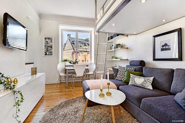 Không gian phòng khách rộng thoáng với chiếc bàn trà nhỏ cùng bộ ghế sofa xám nổi bật trên nền trắng của căn hộ. Phía đối diện là góc trang trí với cây xanh, tủ đồ và một chiếc ti vi được gắn cố định vào tường.