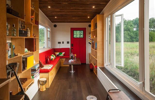 Ngay lối vào nhà là phòng khách hình chữ L nổi bật với tông màu đỏ. Nơi đây được dành riêng một khu vực sáng nhất với view nhìn ra bên ngoài tuyệt đẹp.