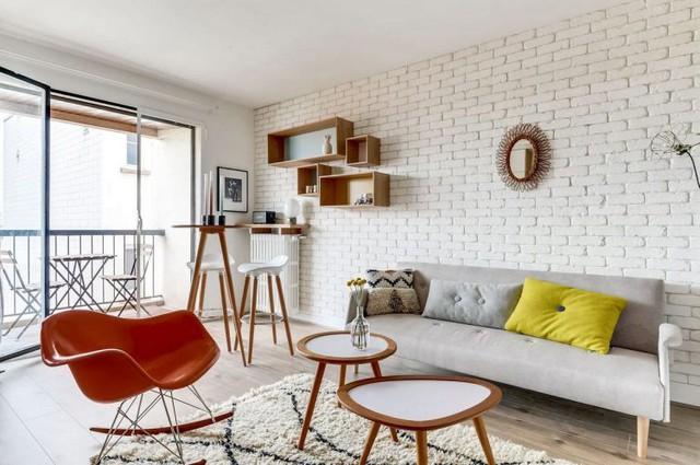 Bên cạnh là những chiếc bàn trà nhỏ xin cùng chiếc ghế bành nhỏ màu cam thêm điểm nhấn tuyệt đẹp cho khu vực này. Điểm ấn tượng nhất trong nhà đó là bức tường gạch thô sơn trắng tạo không gian thân thiện và gần gũi.