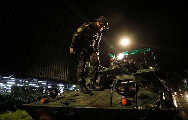 Cảnh sát trên xe bọc thép được huy động tới khu phức hợp Resorts World Manila sau khi nổ súng xảy ra. Ảnh: Reuters