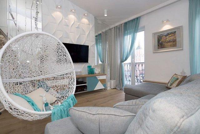 Chiếc võng treo hình tổ chim là điểm nhấn vô cùng ấn tượng trong phòng khách. Bên cạnh đó việc pha trộn giữa màu xanh của rèm cửa và một số đồ nội thất cũng khiến cho căn nhà trở nên đẹp hơn.