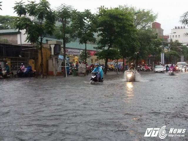 Do mưa kèm sấm chớp nên hầu hết người dân phải trì hoãn việc đi làm, đưa con đi học. Nhiều người đang đi đường vội tấp vào lề, đề phòng nguy hiểm.
