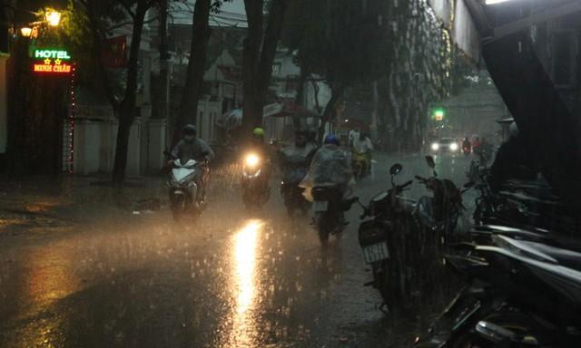 Cơn mưa bất chợt, khiến một số người đi xe máy phải tấp vào lề đường trốn mưa.