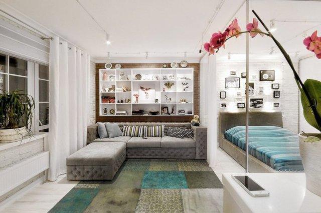 Không gian tiếp khách được chủ nhà ưu ái dành 1 địa điểm đẹp nhất, sáng nhất cạnh cửa sổ. Nơi đấy được bố trí dễ làm có bộ sofa xám và 1 hệ kệ tủ sát tường, nơi trưng bày những món đồ lưu niệm đẹp của chủ nhà.