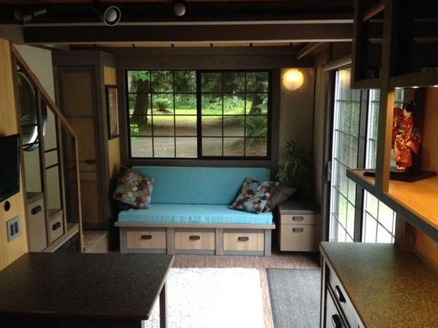 Nhìn bề ngoài căn nhà rất nhỏ nhắn nhưng bên trong không ai nghĩ nó lại thoáng rộng và đầy đủ tiện nghi đến vậy. Ngay lối vào nhà là góc tiếp khách xinh xắn cạnh cửa sổ. bên dưới ghế sofa là những ngăn kéo trữ đồ thuận tiện.