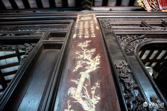Mảng giữa tường và khánh thờ là các bức hoành phi được sơn son thiếp vàng, các bức liễn bằng những câu đối cẩn xà cừ đính trên cột. Gian giữa phía trên là khám thờ với tấm thủ quyển chạm nổi hình Tứ linh, giữa bức thủ quyển là ba hàng chữ đề danh hiệu các vị thần được thờ tự.