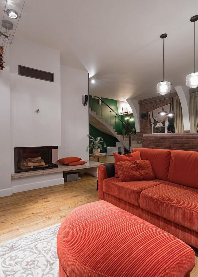 Phòng khách rộng thoáng với bộ sofa đỏ cùng bức chân dung bắt mắt.