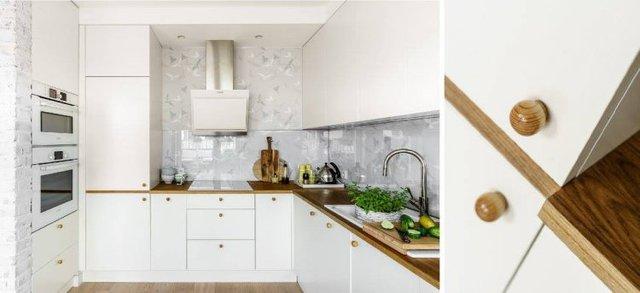 Góc bếp sạch sẽ và tiện nghi với hệ thống tủ kệ khép kín thỏa mãn mọi nhu cầu trữ đồ của chủ nhà. Từng ngăn kéo, cánh tủ đều được gắn một nút đóng mở tròn bằng gỗ rất đẹp.