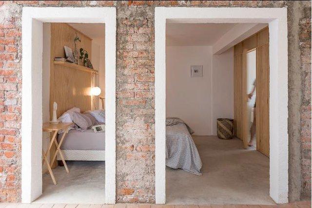 Khu vực đối diện là phòng ngủ, khu vệ sinh và nhà tắm. Bên ngoài là một bức tường gạch thô tạo cảm giác mộc mạc đơn giản cho ngôi nhà.