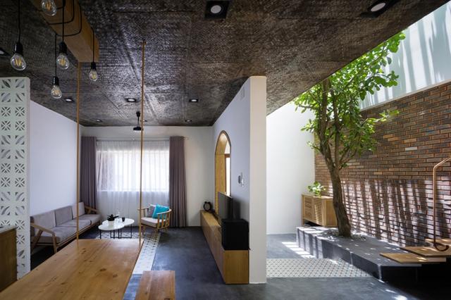 Ngôi nhà được xây dựng 2 tầng. Tầng 1 là không gian dành cho tiếp khách, bếp, bàn ăn và 2 khoảng sân nhỏ với cây xanh.