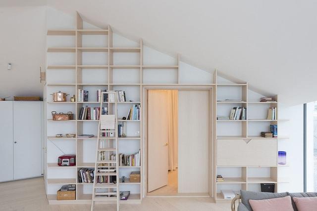 Một hệ kệ gỗ có kích thước rộng lớn cao sát trần nhà. Ẩn bên trong là một phòng nhỏ.