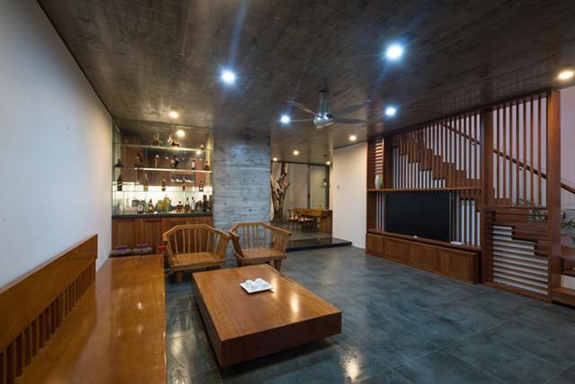 Công trình nằm trong vùng đất thấp, bị ngập lụt về mùa mưa nên nền tầng một được đẩy lên cao so với mặt đường. Không gian phòng khách tuyệt đẹp với bộ bàn ghế gỗ bóng loáng.