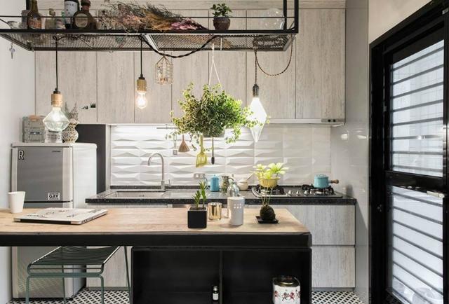 Khu vực bếp và bàn ăn được bố trí ngay cạnh trong cùng một không gian mở thoáng sáng. Góc nhỏ này được thiết kế gọn gàng, sáng bóng với đầy đủ những thiết bị gia dụng tiện nghi. Hệ thống tủ kệ khép kín cả bên trên và bên dưới khiến cho khu bếp nhỏ không bị rối mắt.