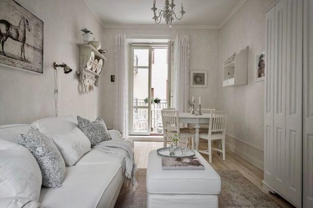 Phòng khách đơn giản với bộ salon kê sát tường để tiết kiệm diện tích và một bàn trà trắng muốt.