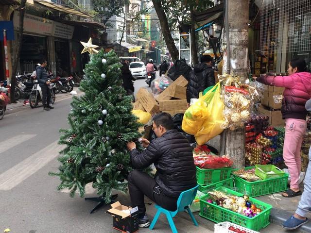 Những người bán hàng trang trí cây thông theo yêu cầu khách hàng.