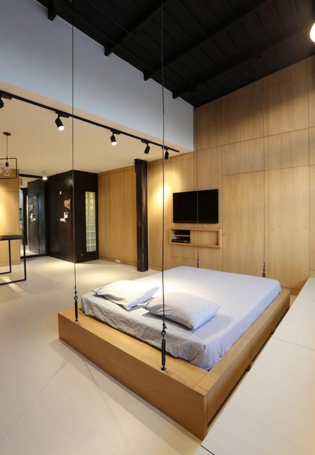 Chạy dọc bức tường cạnh giường ngủ là cả một hệ thống tủ âm tường thỏa mãn nhu cầu trữ đồ cho gia chủ. Để tiết kiệm tối đa diện tích và tạo không gian thông thoáng chiếc ti vi cũng được gắn chặt lên cao.