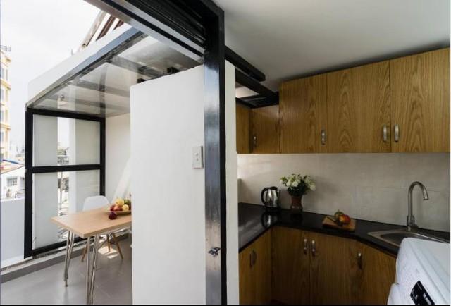 Khu bếp nhỏ méo mó được khéo léo đặt cạnh khoảng bàn ăn bên ngoài.