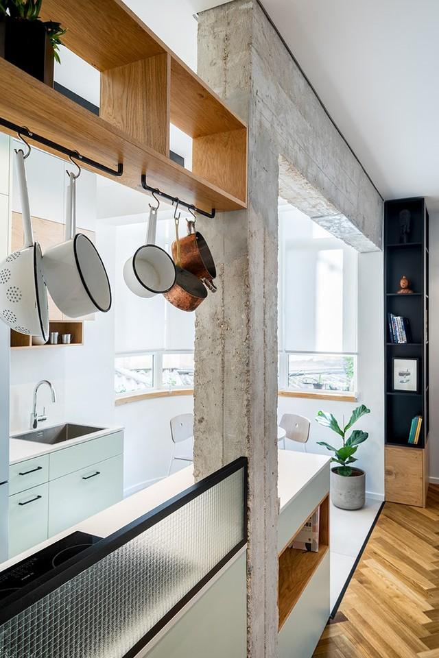 Căn bếp với tông màu trắng tách mình ra khỏi không gian phòng khách. Nhiều chi tiết cột kèo được giữ nguyên vẻ ngoài thô ráp theo ý của chủ đầu tư.