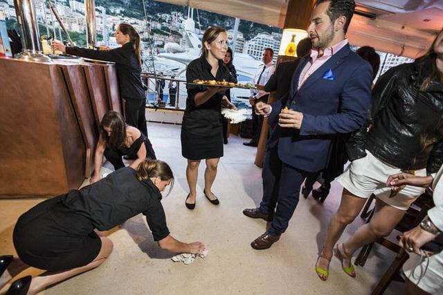 Một nữ tiếp viên lau dọn sàn nhà tại một bữa tiệc được tổ chức bởi nhà sản xuất whisky Johnnie Walker trên chiếc du thuyền dài 157 foot của anh tại Grand Prix Monaco ở Monte Carlo, 2013.
