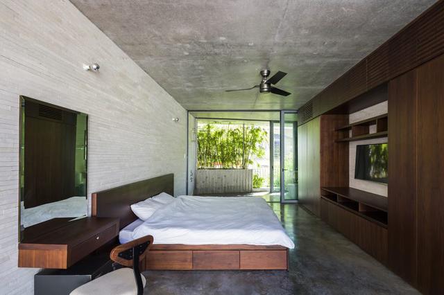 """Không gian phòng ngủ đẹp, thoáng mát mà vẫn bảo đảm kín đáo, riêng tư nhờ một """"tấm rèm đặc biệt"""" được làm bằng bồn cây cao và rặng tre phía trước nhà."""