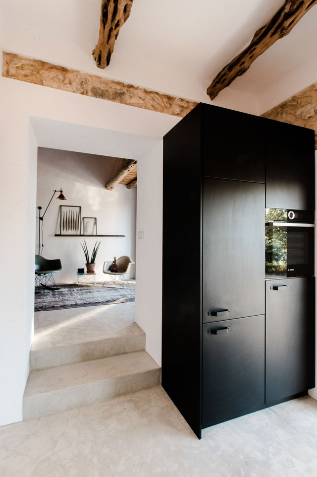 Khu vực bếp và vệ sinh được bố trí ở khối nhà liền kề với nền nhà thấp hơn. Chiếc tủ bếp đen tạo nên vẻ đẹp cá tính và dịu dàng, nổi bật trong không gian sử dụng màu trắng làm tông nền.