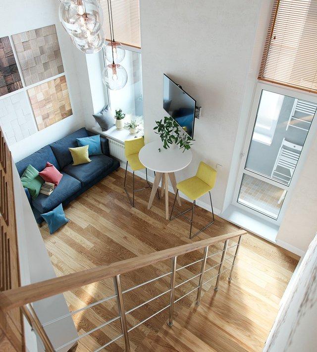 Không gian phòng khách được thiết kế nhỏ xinh cạnh cửa sổ với bộ sofa màu xanh dương đậm cùng những chiếc gối dựa đầy màu sắc. Khung cửa sổ rộng lớn trên cao đủ để cung cấp nguồn sáng tự nhiên cho nơi này trở nên ấm áp và tươi tắn.