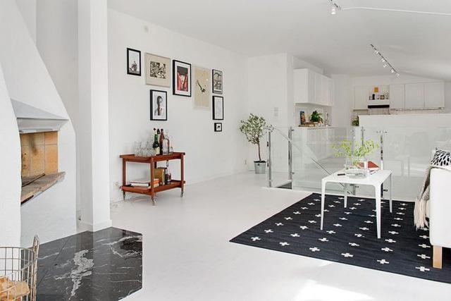 Khu vực bếp và bàn ăn đặt riêng một không gian và ngăn cách với phòng khách bởi cầu thang kính trong suốt.
