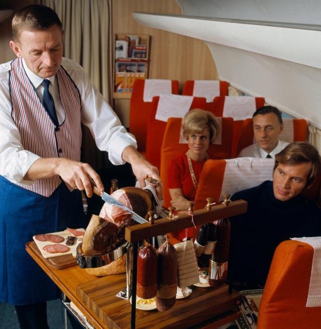 Cảnh một người đầu bếp đang cắt lát thịt đùi lợn muối bằng con dao chuyên dụng to để phục vụ trực tiếp cho các thực khách trên máy bay. Điều này chắc chắn sẽ không thể được cho phép trong các chuyến bay ngày nay (bởi dao hay những vật nguy hiểm đều bị hạn chế trên máy bay vì lí do an ninh).