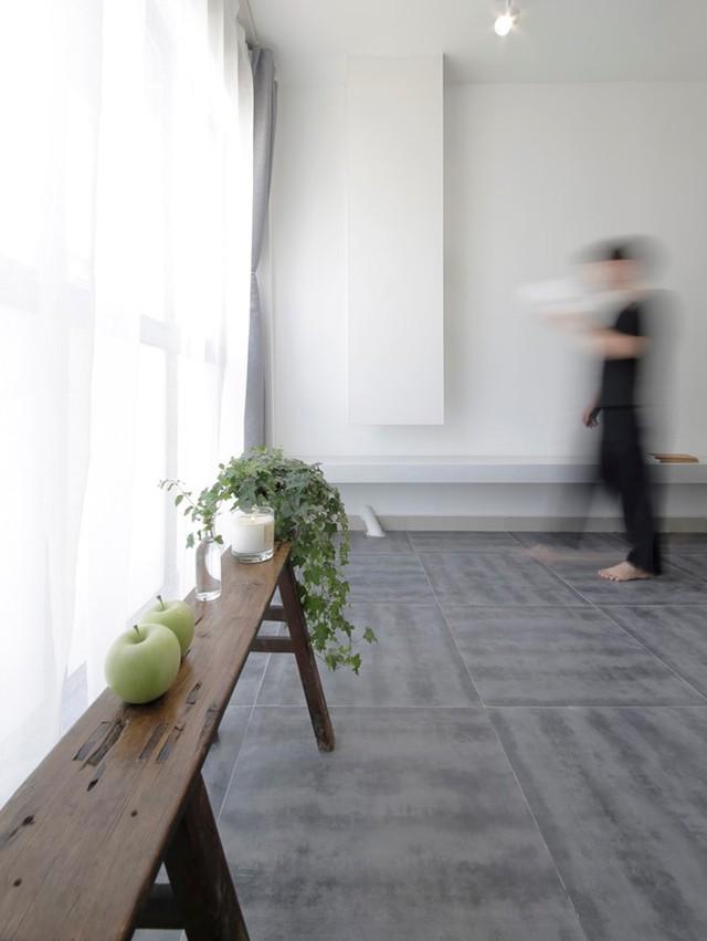 Một chiếc ghế băng dài nhỏ đặt sát tường vừa có vai trò như một chiếc bàn để đồ, nhưng nó cũng vừa là điểm nhấn trang trí bắt mắt cho không gian. Trong căn hộ này cây xanh được ưu ái bố trí ở rất nhiều nơi mang màu xanh tươi mát và sức sống cho căn phòng.