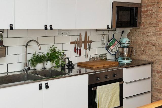 Hệ thống tủ kệ khép kín nơi nấu ăn khiến không gian bếp càng trở nên gọn đẹp. Cây xanh cũng được trồng để mang màu xanh tươi mát cho góc nấu nướng.