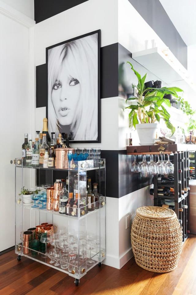 Vốn là người thích nấu ăn và mê các loại đồ uống nên bức tường ngăn cách giữa phòng khách và phòng ngủ là nơi chủ nhà trưng bày các loại rượu và rất nhiều ly cốc.