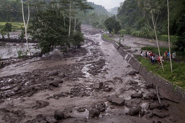 Mưa khiến cho tro bụi từ núi lửa chảy thành dòng nước đục nóng xuống ngôi làng ở phía dưới. Ảnh: Andri Tambunan/Getty Images